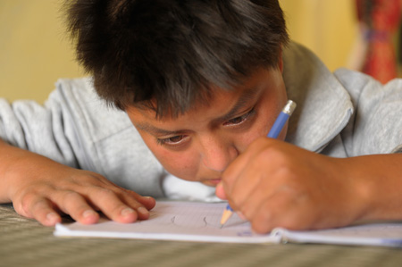 Child writing in Ecuador. Photo courtesy of Compassion International